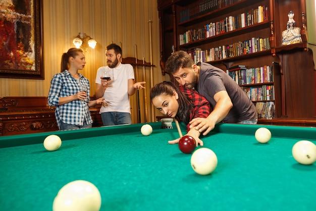 Junge lächelnde männer und frauen, die nach der arbeit billard im büro oder zu hause spielen.