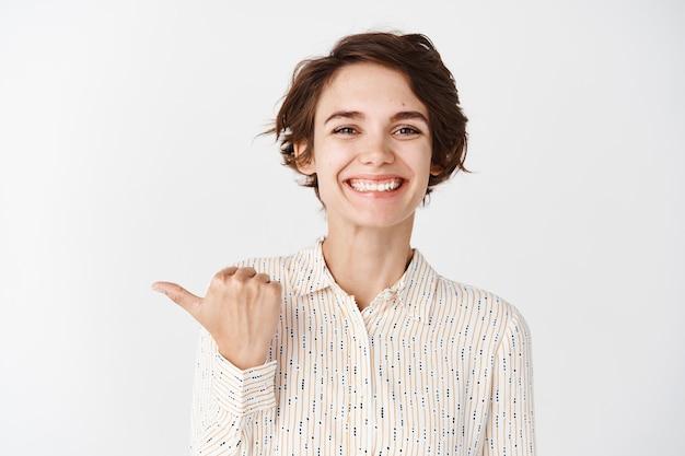 Junge lächelnde mitarbeiterin, die glücklich und stolz aussieht, mit dem finger auf die linke firma zeigt und gegen die weiße wand steht