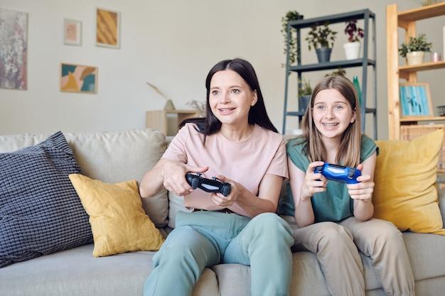 Junge lächelnde mutter und süßes teenager-mädchen mit joysticks, die während des videospiels tasten drücken, während sie auf der couch gegen die regale an der wand sitzen?