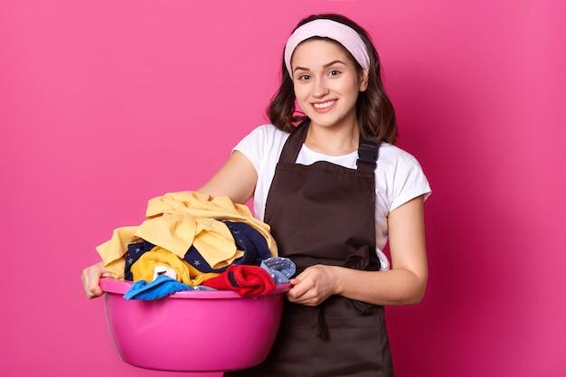 Junge lächelnde niedliche frau, die mit rosa becken geht und viel wäsche hat