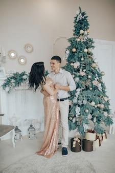 Junge lächelnde paare beim nahe einem weihnachtsbaum zu hause feiern