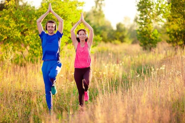 Junge lächelnde paare, die draußen sportliche übungen tun