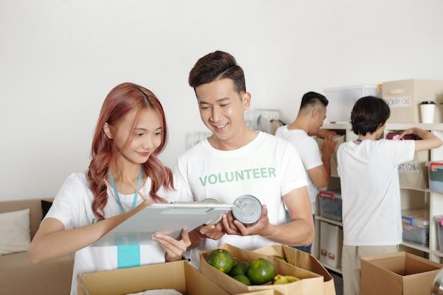 Junge lächelnde paare, die im wohltätigkeitszentrum arbeiten, machen sich notizen in der zwischenablage, wenn sie gespendete kleidung in lebensmitteln auspacken