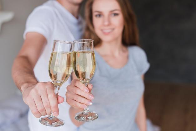 Junge lächelnde paare, die zu hause gläser champagner klopfen