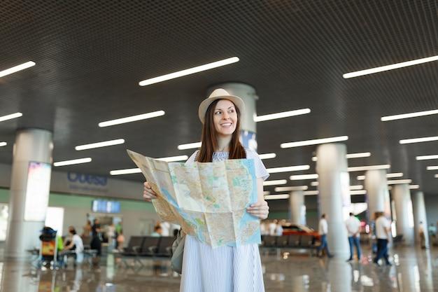 Junge lächelnde reisende touristenfrau mit hut, die papierkarte hält, beiseite schauend, während sie in der lobbyhalle am internationalen flughafen wartet