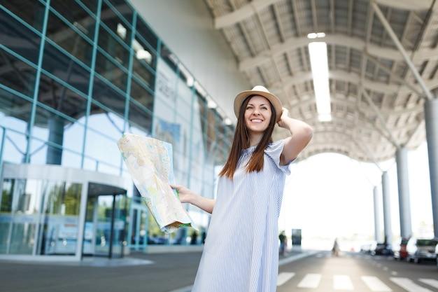 Junge lächelnde reisende touristenfrau mit hut, die papierkarte hält und die hände in der nähe des kopfes am internationalen flughafen hält