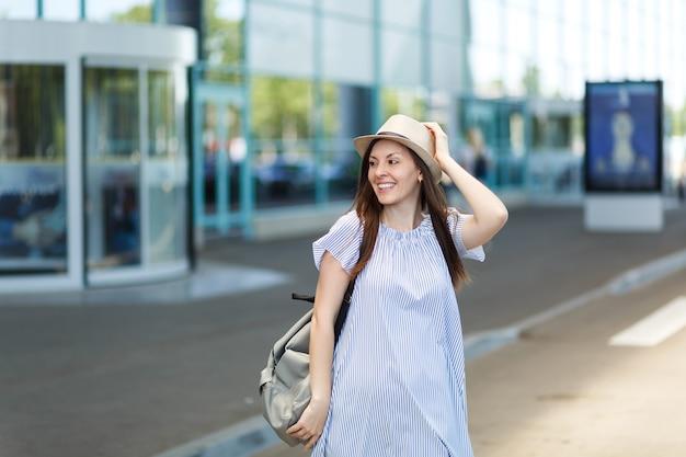Junge lächelnde reisende touristenfrau mit hut mit rucksack, die am internationalen flughafen steht