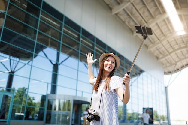 Junge lächelnde reisende touristenfrau mit retro-vintage-fotokamera, die selfie auf dem handy mit egoistischem einbeinstativ am flughafen macht?
