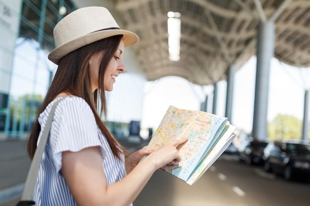 Junge lächelnde reisende touristin mit hut mit rucksack auf der suche nach route in papierkarte am internationalen flughafen?