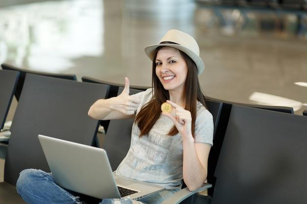 Junge lächelnde reisende touristin mit hut sitzt, arbeitet am laptop, hält bitcoin, zeigt daumen nach oben und wartet in der lobbyhalle am flughafen?
