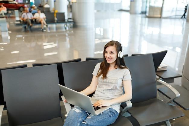 Junge lächelnde reisende touristin mit kopfhörern, die musik am laptop hört, wartet in der lobbyhalle am internationalen flughafen?