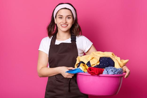 Junge lächelnde schöne frau, die mit rosa becken voller schmutziger kleidungsstücke geht und es mit beiden händen hält, sieht positiv aus. beschäftigte attraktive hausfrau steht isoliert auf rosa.