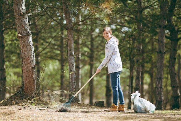 Junge lächelnde schöne frau, die rechen für die müllabfuhr in der nähe von müllsäcken im park oder wald säubert und verwendet. problem der umweltverschmutzung