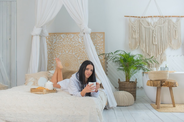 Junge lächelnde schöne frau im weißen hemd, die morgens auf dem bett aufwacht hübsche frau, die croissants hält und eine tasse kaffee im schlafzimmer trinkt konzept des lebensstils des essens