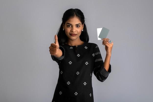 Junge lächelnde schöne frau oder mädchen, die kreditkarte in der hand darstellt, die vertrauen und zuversicht für die zahlung zeigt.