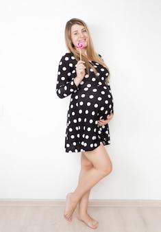 Junge lächelnde schwangere frau, die mit lutscher aufwirft