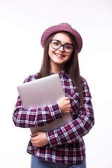 Junge lächelnde selbstbewusste frau, die laptop-computer und schauende kamera lokalisiert über weißem hintergrund verwendet