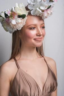Junge lächelnde sinnliche dame im kleid mit schönem blumenkranz
