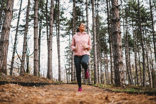 Junge lächelnde sportlerin mit gesunden gewohnheiten, die im herbst im wald laufen und sich auf marathon vorbereiten