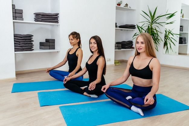 Junge lächelnde sportliche frau und eine gruppe von leuten, die yoga-lektion praktizieren