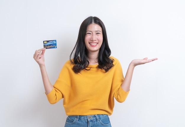 Junge lächelnde und schöne asiatische frau, die kreditkarte in der hand darstellt, die vertrauen und zuversicht für die zahlung zeigt