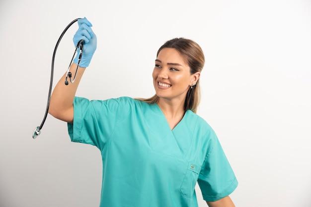 Junge lächelnde weibliche krankenschwester, die mit stethoskop aufwirft.