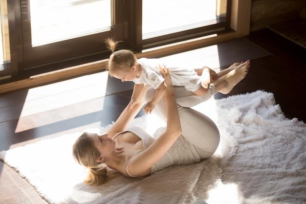 Junge lächelnde yogamutter und babytochter, die zu hause trainiert
