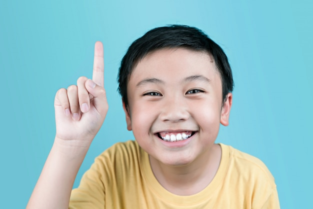 Junge lächelt und zeigt den finger.