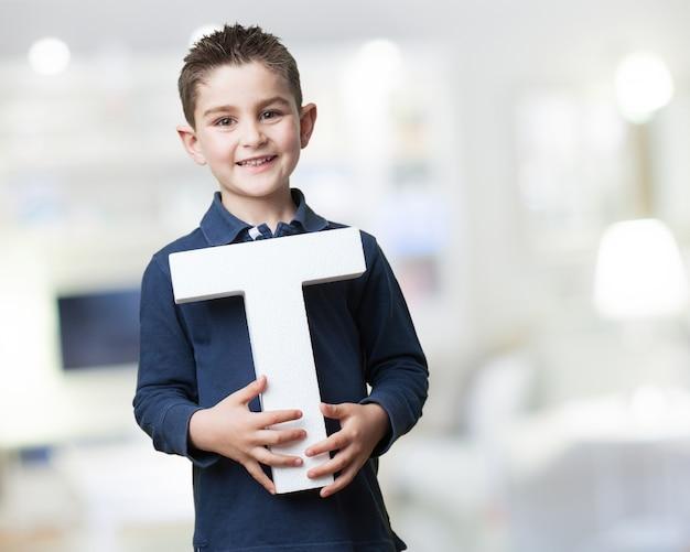 Junge lächelt, während er den buchstaben