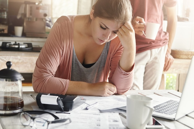Junge lässige frau, die depressiven blick hat, während familienfinanzen verwaltet und papierkram erledigt, am küchentisch mit vielen papieren, taschenrechner und laptop sitzend