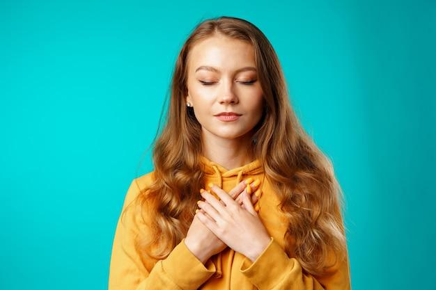 Junge lässige frau, die hände auf ihrer brust und augen geschlossen hält