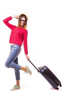 Junge lässige frau, die mit reisekoffer steht - lokalisiert auf weißer wand. berufungskonzept