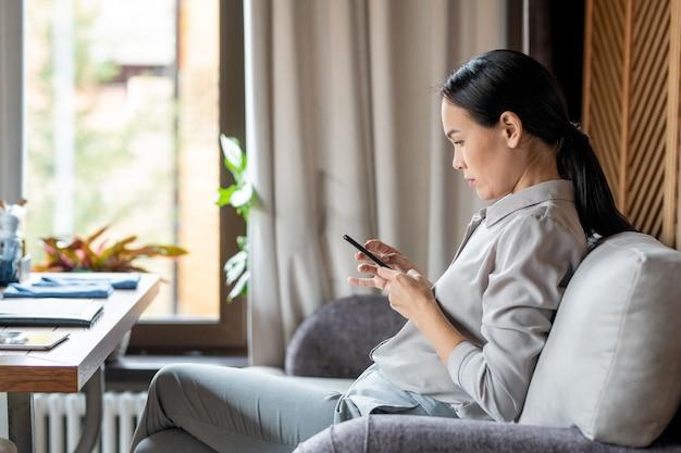 Junge lässige frau mit smartphone, das auf couch im restaurant und in der nachricht sitzt, während auf jemanden wartet
