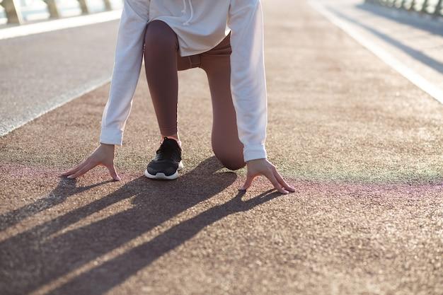 Junge läuferfrau in der ausgangsposition ist bereit zu laufen. platz für text