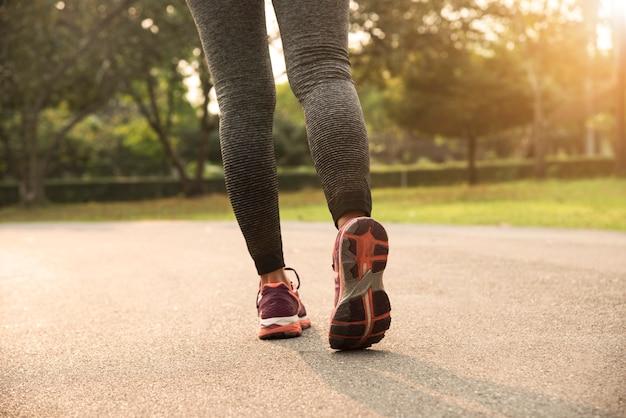 Junge läuferfrauen, die an der straße mit sonnenunterganghintergrund rütteln.