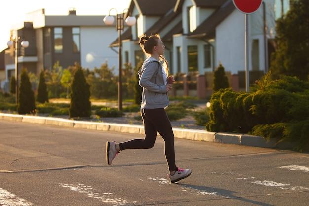 Junge läuferin, athletin joggt in der stadtstraße bei sonnenschein. schönes kaukasisches frauentraining, musik hören