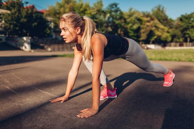 Junge läuferin, die im sommer früh auf dem sportplatz startet. aktiver gesunder lebensstil