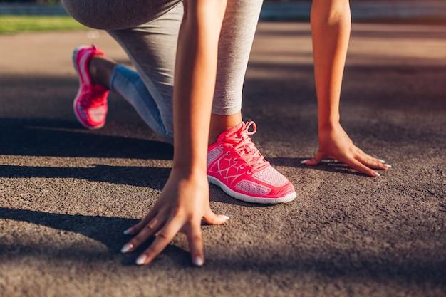 Junge läuferin, die im sommer früh auf dem sportplatz startet. nahaufnahme von turnschuhen und händen. aktiver lebensstil