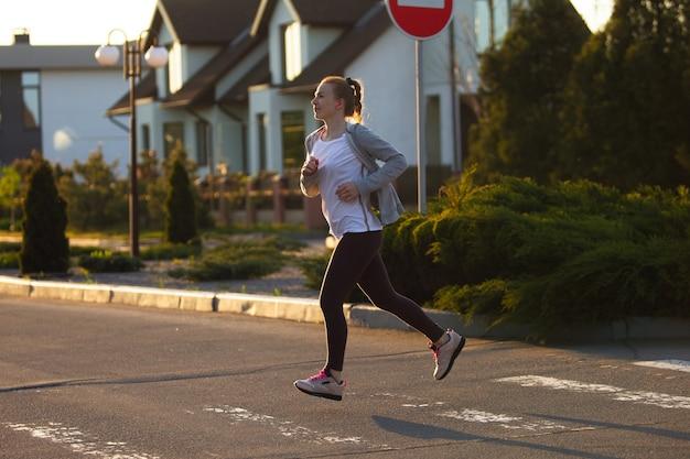 Junge läuferin joggt in der stadtstraße bei sonnenschein schöne kaukasische frau