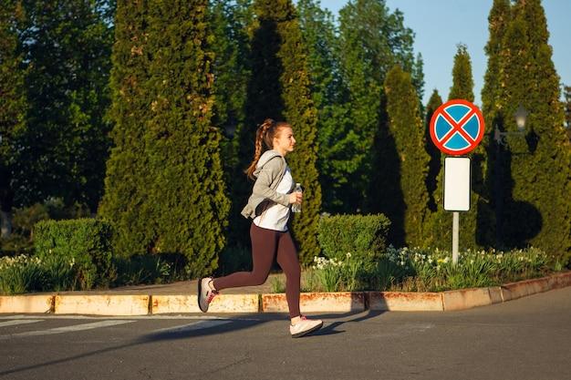 Junge läuferin joggt in der stadtstraße bei sonnenschein
