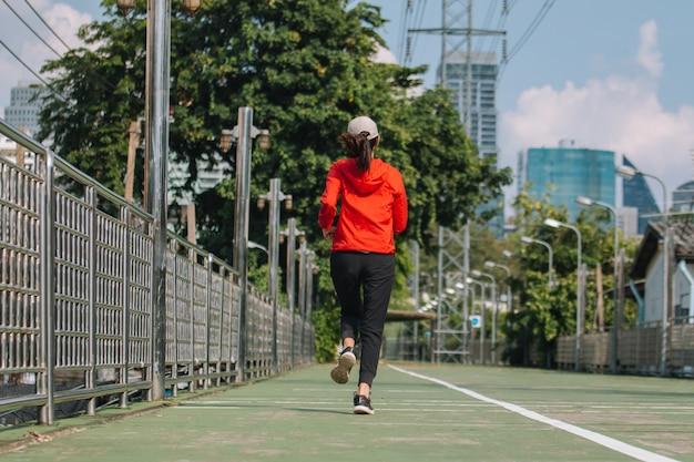 Junge läuferinnen auf der straße laufen für übung auf stadtstraße; sport-, menschen-, bewegungs- und lifestyle-konzept