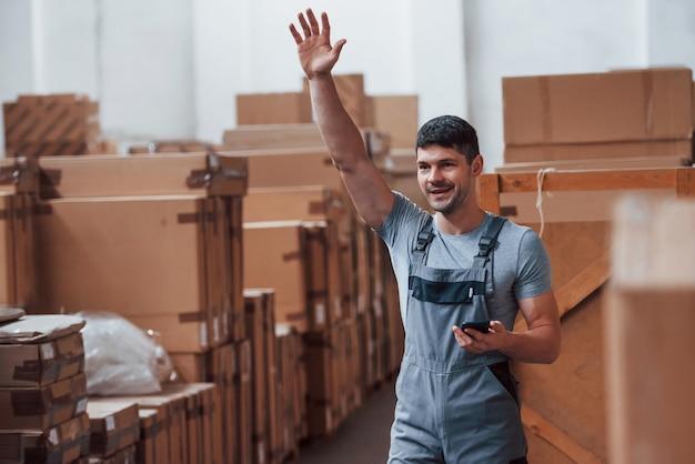 Junge lagerarbeiter in uniform mit telefonständern und erhobener hand.