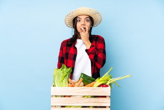 Junge landwirt frau, die frischgemüse in einem hölzernen korb überrascht und beim schauen entsetzt hält