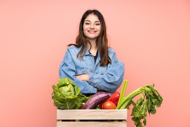 Junge landwirtfrau, die einen korb voll vom frischgemüselachen hält
