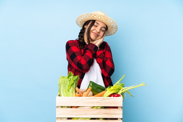 Junge landwirtin, die frisches gemüse in einem hölzernen korb hält, der schlafgeste in dorable ausdruck macht
