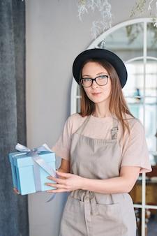 Junge langhaarige frau in schürze, hut und brille hält blaue geschenkbox gebunden mit weißem seidenband