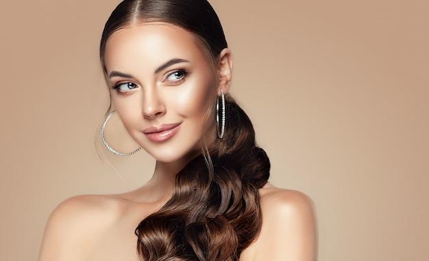 Junge langhaarige schöne frau schaut mit interesse make-up und kosmetik beiseite