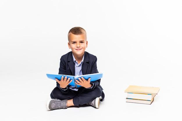 Junge las buch, das auf dem boden auf einer weißen wand sitzt