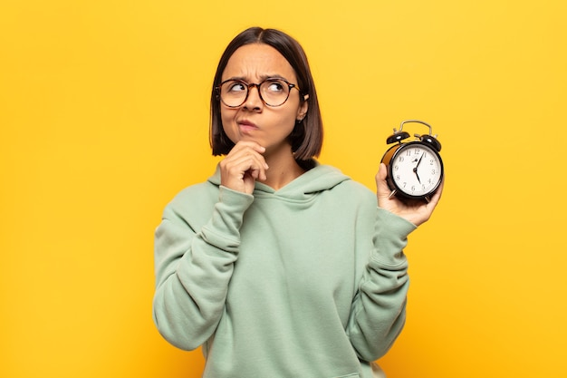 Junge lateinamerikanische frau denkt, fühlt sich zweifelhaft und verwirrt, hat verschiedene möglichkeiten und fragt sich, welche entscheidung sie treffen soll