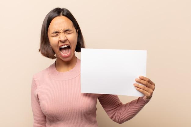 Junge lateinamerikanische frau, die aggressiv schreit, sehr wütend, frustriert, empört oder genervt aussieht und nein schreit